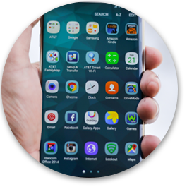 Image of a person holding a phone with mobile applications on the page